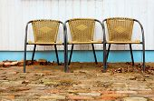 Three Chairs By White Wall