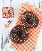 Colorful donuts on white wooden table, selective focus