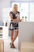 Portrait of pretty blond woman texting on mobile phone, standing in living room, wearing mini dress and high heel shoes.