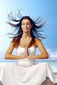 Attractive young woman meditating on the beach eyes closed, wind blowing hair, smiling, sitting in p