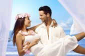 Young man holding happy bride in arms after exotic wedding on tropical island.