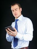 Handsome businessman using computer plane-table, isolated on black background
