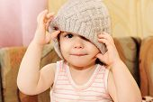 pic of knitted cap  - Close up portrait of adorable baby wearing knit winter cap - JPG