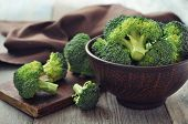 foto of section  - Bunch of fresh green broccoli on brown plate over wooden background - JPG