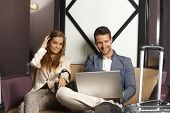 Young couple sitting in hotel lobby, using laptop computer, smiling.