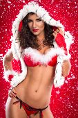 Sexy Santa helper over red background with snow