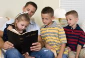 stock photo of role model  - A father reads to his three young children from the Holy Bible - JPG