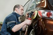 stock photo of wiper  - auto mechanic worker polishing bumper car at automobile repair and renew service station shop by power buffer machine - JPG