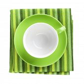 Green coffee cup over kitchen towel. View from above. Isolated on white background