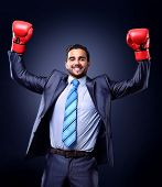 Businessman in a suit and boxing gloves, celebrating a win, isolated on black background