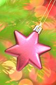 christmas decoration, pink Christmas star ball hanging on spruce twig against bokeh background