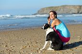 image of working-dogs  - Joyful fitness woman with dog on beach taking a break from running - JPG