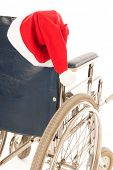wheel chair with red hat Santa Claus isolated over white background