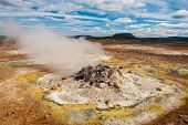 Fumarole in the geothermal area Hverir, Iceland. The area around is multicolored and cracked.