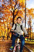 Kids On A Bike In Autumn Park