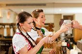 Two young women in traditional Bavarian Tracht sitting in restaurant or pub with beer
