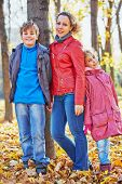 Mother and her two children stand leaning to tree trunk in autumn park