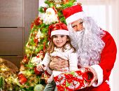 Portrait of little girl receive gift box from Santa Claus, sitting near decorated Christmas tree, happy childhood, Christmastime children's party