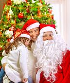 Christmas party, happy family at home celebrating New Year, mother with daughter and Santa claus nea