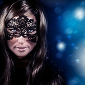 Closeup portrait of beautiful stylish woman wearing mask, luxury New Year party, masquerade in Christmas eve, beauty and fashion concept