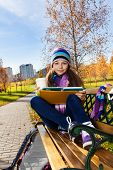 picture of 11 year old  - Portrait of nice smiling 11 years old girl holding coffee mug and textbook wearing blue purple hat and scurf sitting on the bench in the park