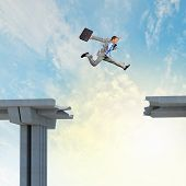 stock photo of interrupter  - Businessman jumping over a gap in the bridge as a symbol of bridge - JPG