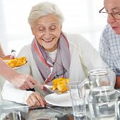 Happy senior citizen couple eating lunch in nursing home