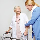 Geriatric nurse helping senior citizen woman with walker