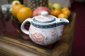 Chinese teapot and fruits.