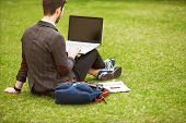 Young Fashion Male Student Sitting On Grass In Park And Holding A Laptop