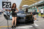 SEPANG, MALAYSIA - MAY 11, 2014: The Reiter Vattana RPM Motorsport grid girl poses with the team car