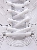 Closeup of the laces on a brand new sneaker. The athletic shoe is all white as are the laces filling