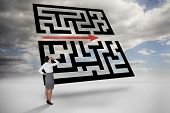 Businesswoman scratching her head against maze with arrow in sky