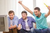 friendship, sports and entertainment concept - happy male friends with vuvuzela watching sports on t
