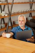 senior man with notebook sitting at the kitchen and drink coffee
