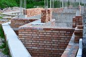 stock photo of reinforcing  - Retaining wall red brick masonry and reinforced concrete pillars on house under construction - JPG