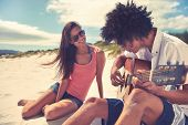 stock photo of couple sitting beach  - Cute hispanic couple playing guitar serenading on beach in love and embrace - JPG