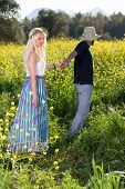 Young Man Leading His Girlfriend Through Rapeseed