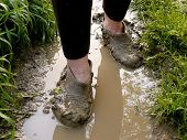 walking through the rain puddle in the muddy rubbers