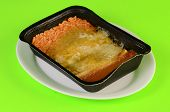 image of enchiladas  - Frozen microwave Mexican Dinner in black plastic tray on white plate against lime green background - JPG