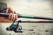 Hand Holding A Fishing Rod With Ree