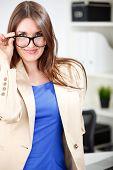 woman wearing glasses posing in office dress
