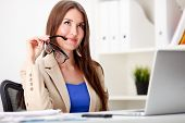 woman holding glasses in hand and working in office