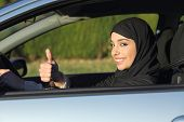 Happy Arab Saudi Woman Driving A Car With Thumb Up