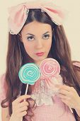 cute young woman dressed as a doll holding lollipop