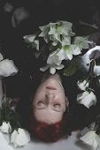 Relaxing, Teen submerged in water with white roses, romance scene