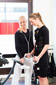 Female coach controlling results after ems electro muscular stimulation training with body fat measu