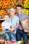 Happy family against shelves of fruits goes shopping. Father keeps a packet with fruits and son sits