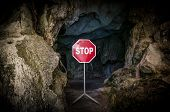 Entry To Dark Cave Blocked With Stop Sign.