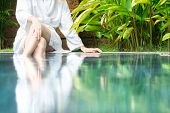stock photo of white gown  - Slim woman in white bathrobe sitting at pool in hotel with her feet in blue clear water - JPG